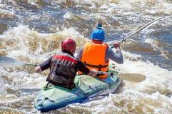 漂流,划皮船 运动器材的两位运动员在一条开水小河的橡胶可膨胀的小船航行 库存照片