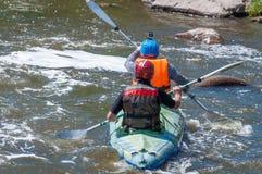 漂流,划皮船 运动器材的两位运动员在一条开水小河的橡胶可膨胀的小船航行 库存图片