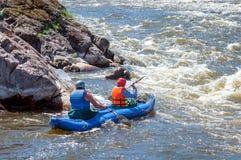 漂流,划皮船 运动器材的两位运动员在一条开水小河的橡胶可膨胀的小船航行 免版税图库摄影