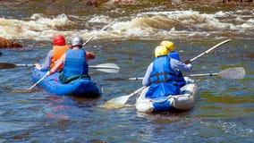 漂流,划皮船 运动器材的运动员在一条开水小河的橡胶可膨胀的小船航行 免版税图库摄影