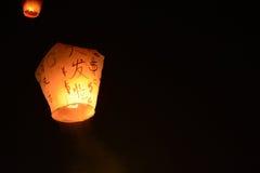 漂浮入夜空的天空灯笼在节日在平溪,中国文本是金钱的一个愿望在新年 库存图片