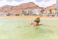 漂浮咸水,死海的少妇旅游游泳 免版税库存图片