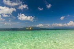 漂浮在一个热带海岛的海岸的小船 酸值张 免版税库存图片