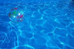 漂浮在一个蓝色游泳池的海滩球 夏天背景 库存图片