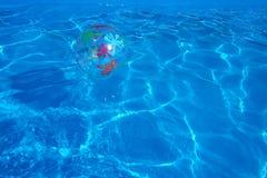 漂浮在一个蓝色游泳池的海滩球 夏天背景 免版税库存照片