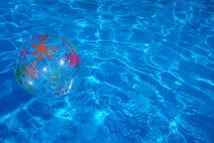 漂浮在一个蓝色游泳池的海滩球 夏天背景 免版税库存图片