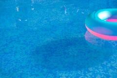 漂浮在一个透明的水池的五颜六色的救生衣 免版税库存图片