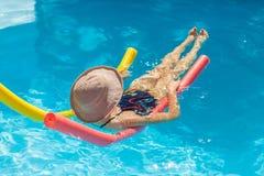 漂浮在一个水池在戴帽子的夏天 免版税库存照片
