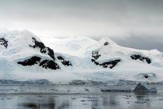漂浮在一座积雪的山的基地的冰山 图库摄影
