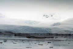 漂浮在一座积雪的山的基地的冰山 库存照片