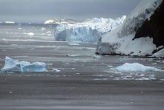 漂浮在一座积雪的山的基地的冰山 免版税库存照片