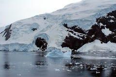 漂浮在一座积雪的山的基地的冰山 免版税库存图片