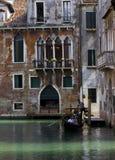 漂浮在一条传统威尼斯式运河的威尼斯平底船的船夫 图库摄影