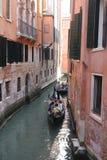 漂浮在一条传统威尼斯式运河的威尼斯平底船的船夫 库存图片