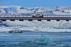 漂浮在一辆通过的汽车下的蓝色冰山在Jokulsarlon冰川盐水湖 库存照片