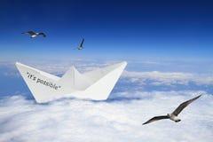 漂浮在云彩的Origami小船 免版税库存照片