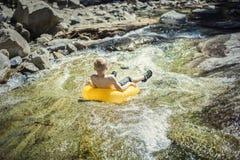 漂浮在他可膨胀的管的一条山河下的男孩 免版税库存照片