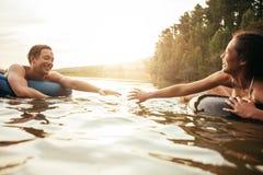 漂浮在内胎的富感情的年轻夫妇在湖 库存照片