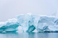 漂浮在南极州的美丽的土耳其玉色冰山,反对有雾的背景 免版税库存图片