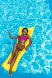 漂浮在可膨胀的床垫的非裔美国人的妇女 免版税库存图片