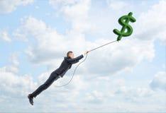 漂浮在天空的商人拿着在atring的大绿色美元的符号 免版税库存照片