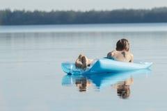 漂浮在天蓝色的可膨胀的水池休息室的后面观点的轻松的十几岁的男孩户外 图库摄影