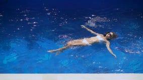 漂浮在她的白色游泳衣的苗条女孩在水池 享受假期的美丽的少妇在 股票录像