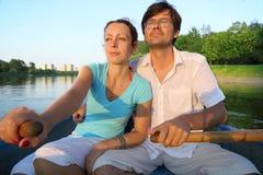 漂浮在小船的河下的年轻夫妇 免版税库存图片