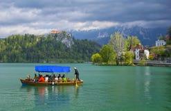 漂浮在布莱德湖的一条小船的小组游人 库存图片