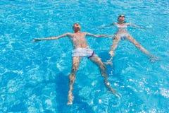 漂浮在手段游泳池的后面的夫妇 库存照片