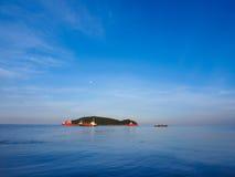 漂浮在有月亮和蓝天的海岛附近的大船 库存图片