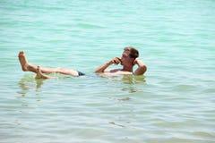 漂浮在死海的年轻可爱的人 免版税库存照片