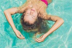 漂浮在水池松弛顶视图的美丽的少妇 holida 免版税库存照片
