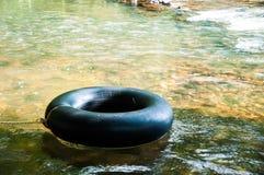 漂浮在水的黑救生圈 免版税库存照片