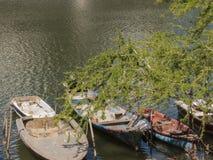 漂浮在河的老小船 免版税库存图片