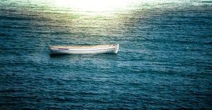 漂浮在波浪的偏僻的小船 免版税库存图片