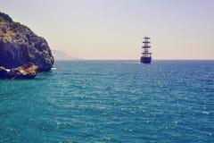 漂浮在海和岩石岸的船 免版税库存照片