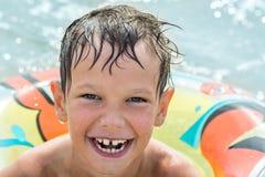 漂浮在海的可膨胀的圆环的男孩所有湿和愉快 库存照片