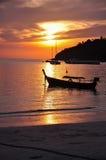 漂浮在海的小船的剪影在日落期间 免版税库存图片