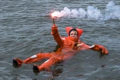 漂浮在生存衣服的人拿着红色handflare 免版税库存照片