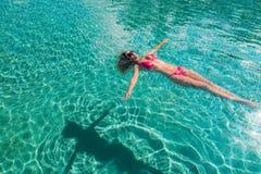 漂浮在深游泳池的红色比基尼泳装的性感的妇女 库存照片