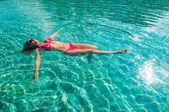 漂浮在深游泳池的红色比基尼泳装的性感的妇女 免版税库存图片