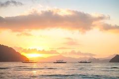 漂浮在温暖的日落光, El Nido,菲律宾的传统菲律宾小船 免版税库存照片