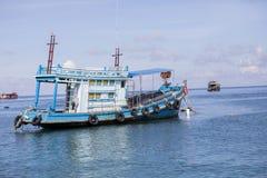 漂浮在港口口岸的蓝色木渔场小船 图库摄影