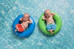 漂浮在游泳圆环的双男婴 免版税库存照片