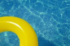 漂浮在游泳池的五颜六色的可膨胀的管 免版税库存照片