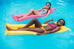 漂浮在游泳池的可膨胀的床垫的年轻不同种族的妇女 库存图片