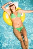 漂浮在游泳池的可膨胀的管的绿色比基尼泳装的愉快的妇女 库存照片