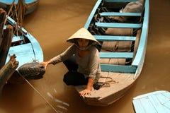漂浮在湄公河的黄色水的一条小船的越南妇女 库存照片