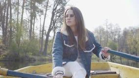 漂浮在湖或河的一条小船的一个逗人喜爱的女孩和牛仔布夹克的画象玻璃的 美丽的浅黑肤色的男人是 股票视频